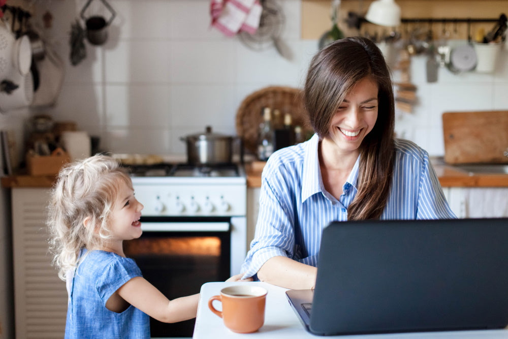 mother and daughter in kitchen using laptop
