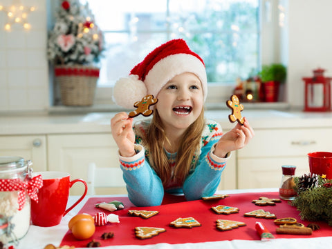 girl with christmas cookies and santa hat
