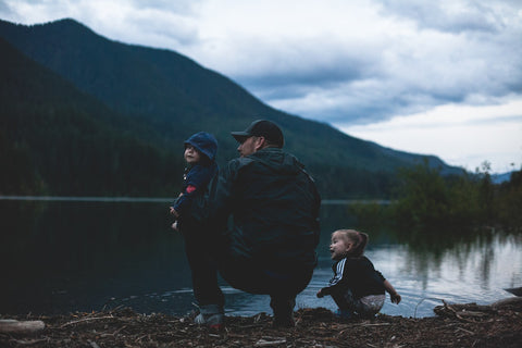father and two children at a lake