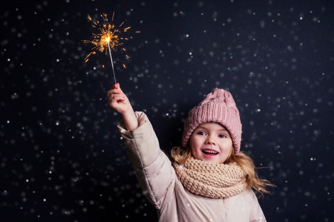 child holding sparkler for virtual new year's eve party
