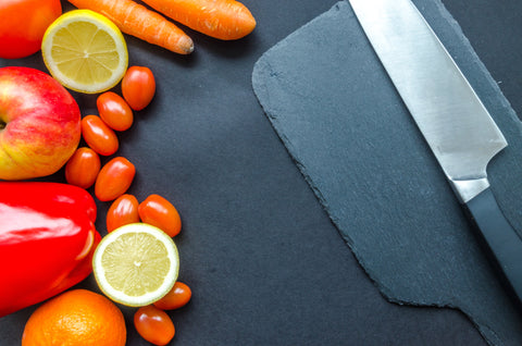 cutting board with vegetables and chef's knife