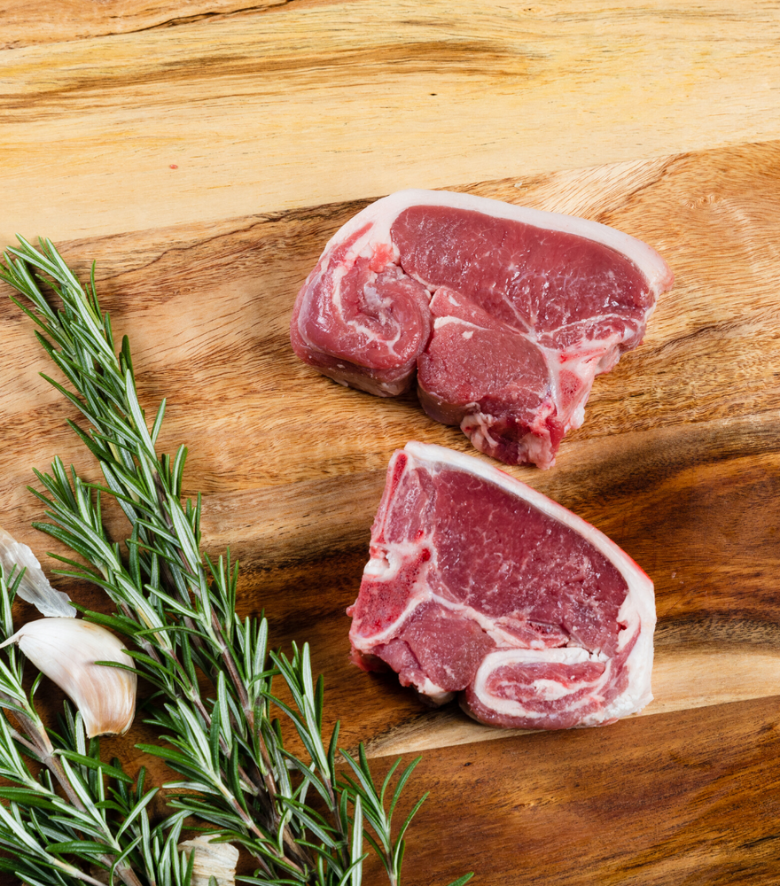 2 fresh versatile cut Rhug Estate Organic Welsh Lamb Loin Chops with garlic and rosemary by side