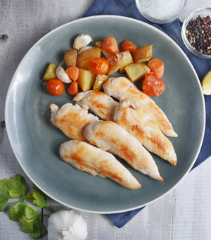 Load image into Gallery viewer, Deliciously cooked Sutton Hoo British Free Range Chicken Mini Fillets with tomato, carrot and potato on a blue plate