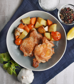 Deliciously cooked Sutton Hoo British Free Range Chicken Thighs with tomato, carrot and potato on a blue plate