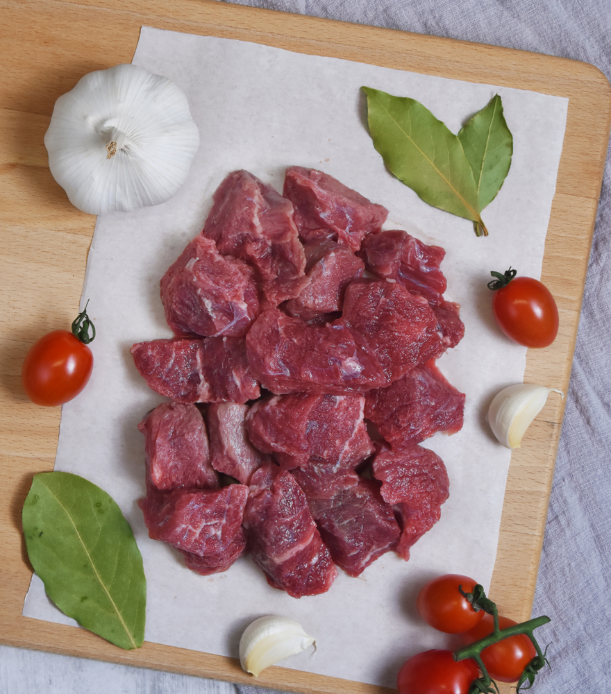 A large portion of fresh New Zealand Angus diced beef with garlic, red grape tomato and bay leaves by side