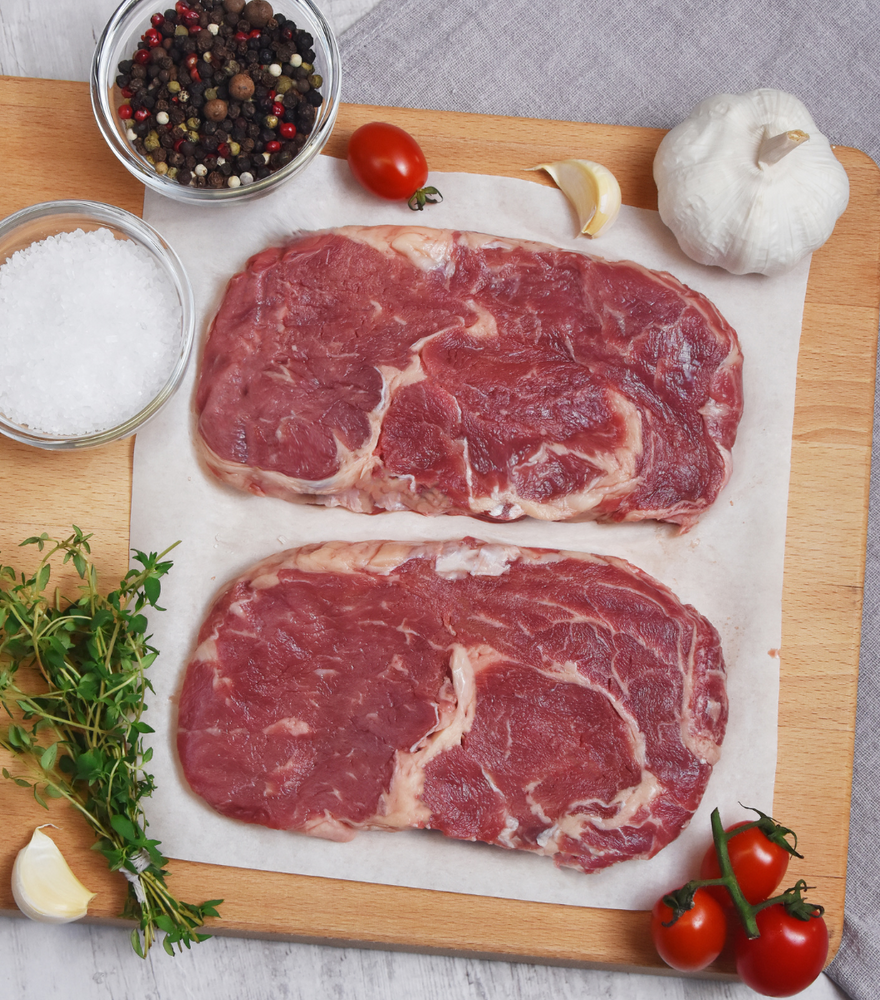 2 slices perfect cut of fresh Green Meadows New Zealand Angus Beef Ribeye Steak with red grape tomato, garlic and spices