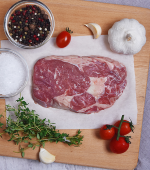 Load image into Gallery viewer, Fresh, tender and generous marbling throughout Angus Beef Ribeye Steak with spices, garlic and red grape tomato.