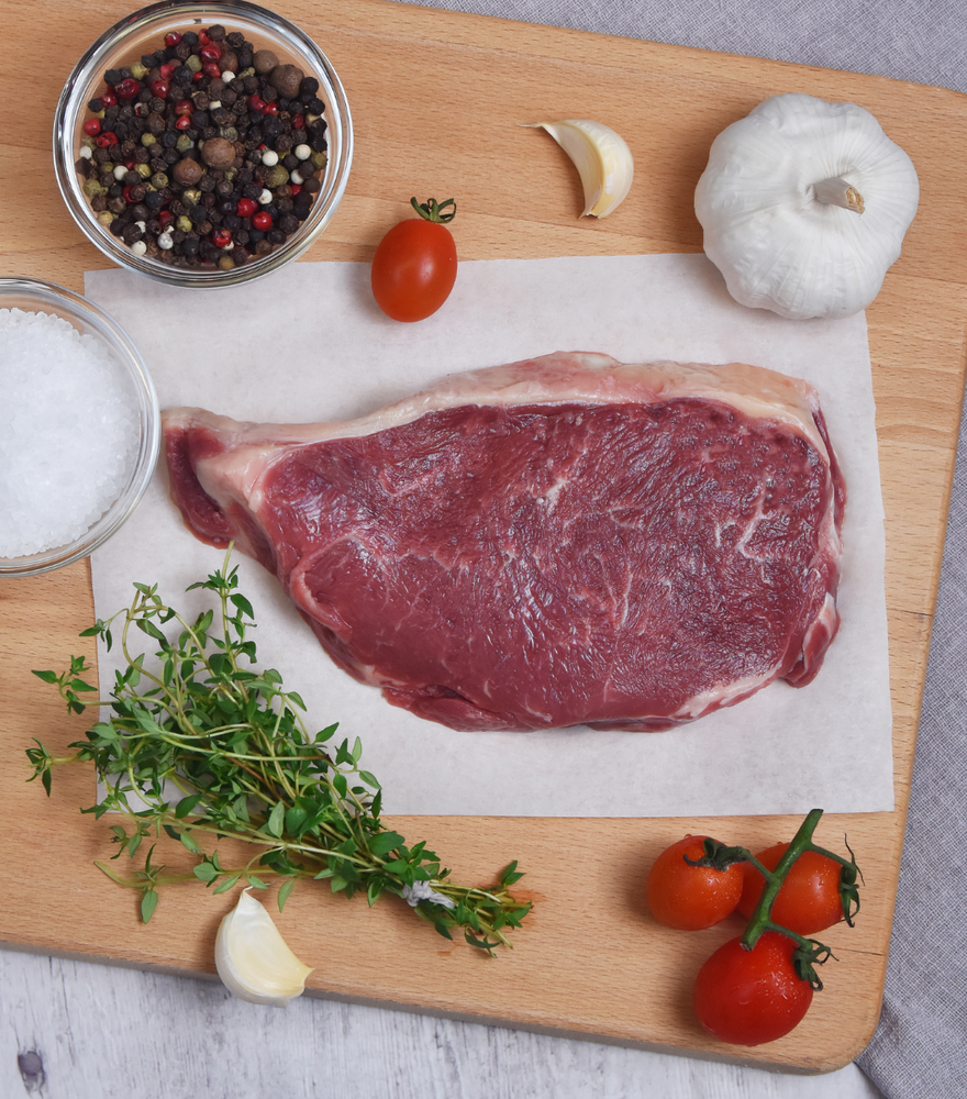 Large serving of  fresh Organic Aberdeen Angus Beef Sirloin Steak with red grape tomato, garlic and spices