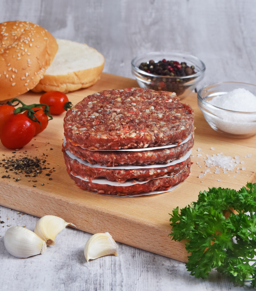 Delicious homemade New Zealand Angus Beef & Sweet Potato Burgers with fresh burger, garlic and spices by side