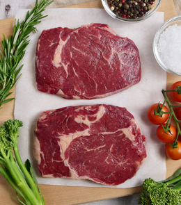 2 Large serving of deliciously grilled Woodburn New Zealand Grass-Fed Beef Ribeye Steaks with garlic by side
