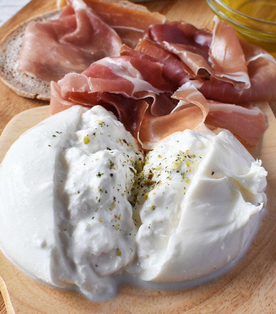 Handmade and delicate Italian Burrata Pugliese paired with stuffed frayed mozzarella and cream