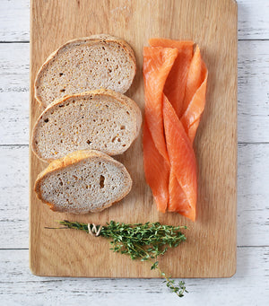 Load image into Gallery viewer, Bread slices, thyme and NZ fresh water cold smoked King salmon on wood board