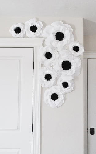 White with Black Center Poppy Flowers mounted to the wall
