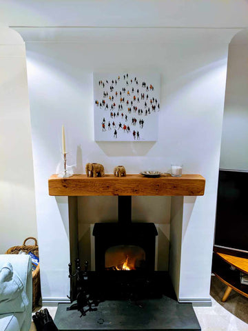 Square wall art looks great over the fireplace in a light and modern room.