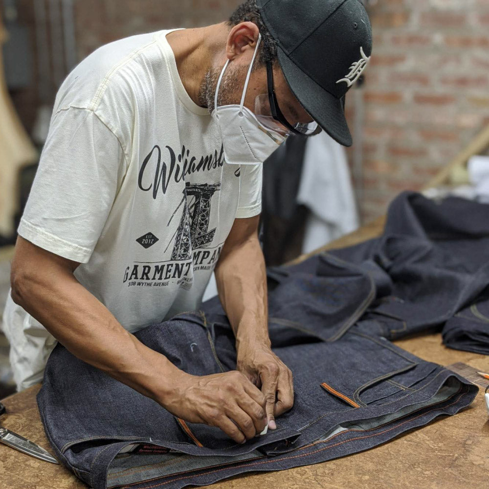 Denim designer Maurice Malone working on custom made jeans in mask during COVID-19