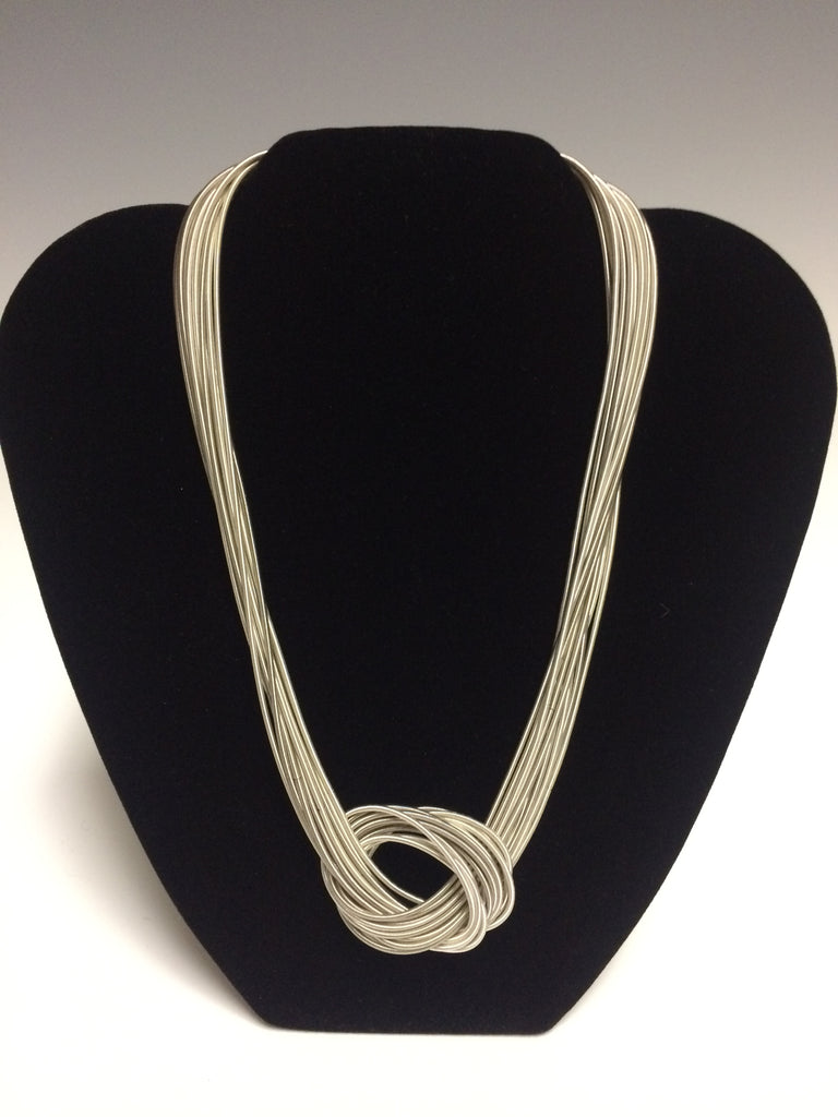 "Made from fine strands of light gray silvertone piano wire this is a perfect gift for the music lover in your life. A heavy duty magnetic closure makes it easy to put on and take off. 18""."