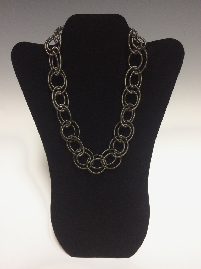 "This hand made slate toned piano wire necklace adds a touch of simple elegance to any outfit. The magnetic closure makes it easy to put on and take off. About 1"" wide and 18"" long."