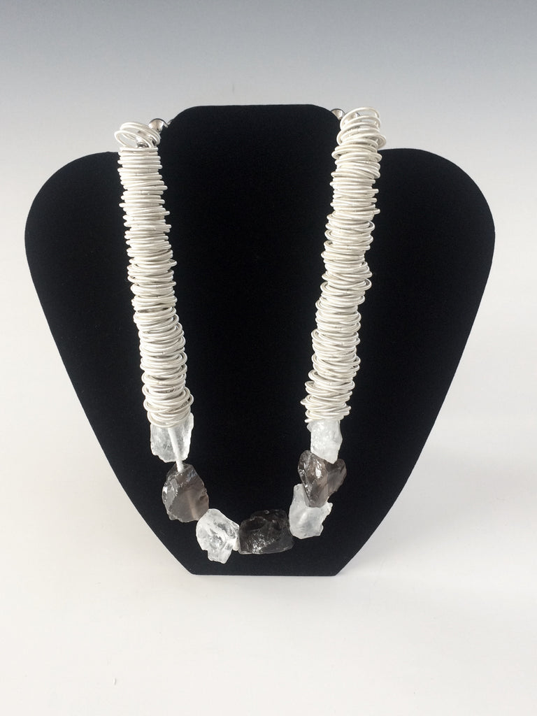 "Made from fine silvertone piano wire and alternating nuggets of textured smokey and white quartz this is the perfect gift for the music lover in your life. A heavy duty magnetic closure makes it easy to put on and take off. 19""."