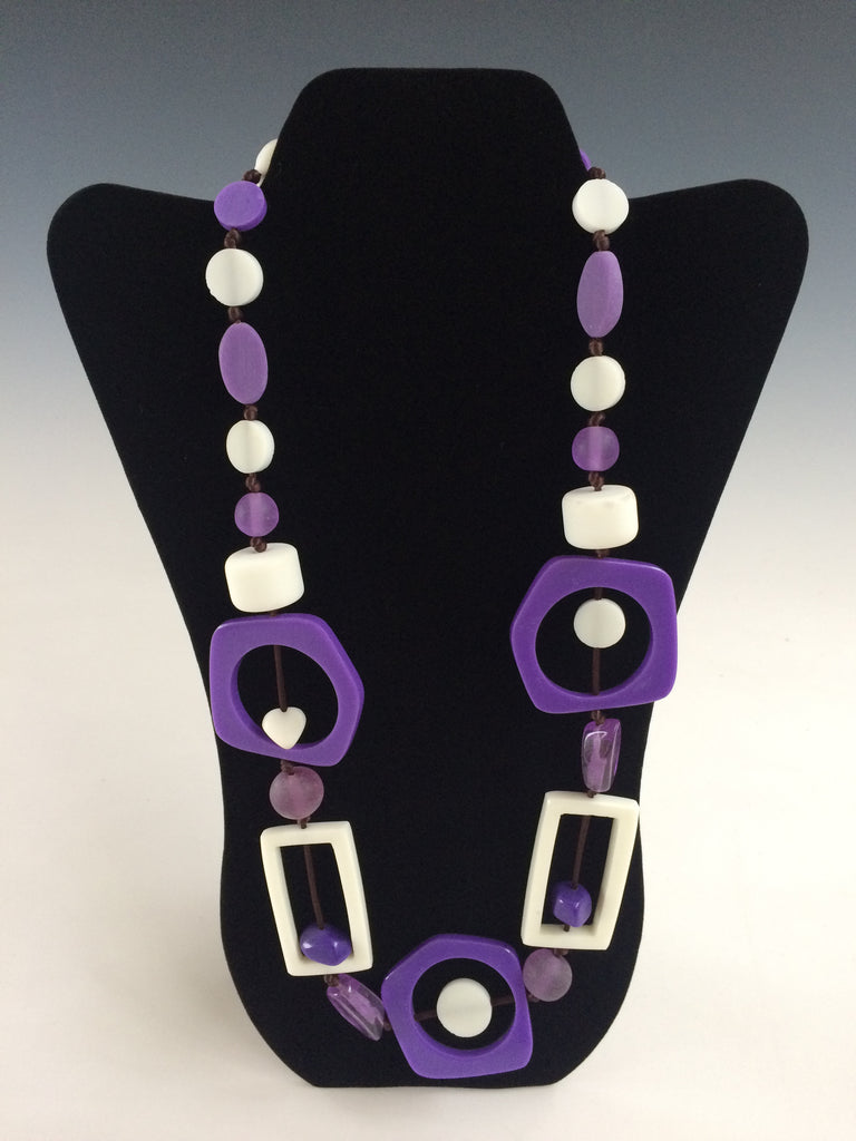 "Make a big statement with this lightweight necklace! Geometric shapes in white and purple resin add a touch of care free fun to any ensemble, and it's so light you can wear it all day long. 28""."