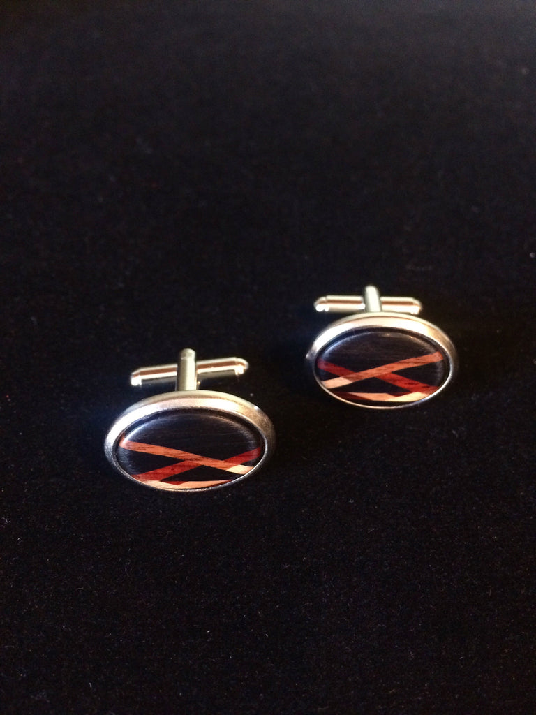 "Cuff links are one of the smallest and smartest accessories in a man's wardrobe. They add sophistication to a casual outfit and polish to a formal suit. Handsome cuff links always make a great impression at a job interview or at the day to day office environment. These cuff links are hand made in America with silver plated brass hinged finding and an inlay face of cherry, maple and cocobolo woods. 7/8"" diameter."