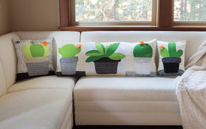 Finished cactus accent pillows made from the Cactus Applique Pillows Sewing Pattern by Jennifer Jangles, displayed on a couch