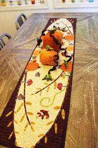 A Walk in the Woods Fall Table Runner Applique Sewing Pattern by Jennifer Jangles displayed on a table with decorative fabric pumpkins