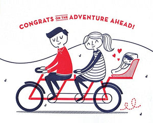 "baby bicycle good paper greeting card features a couple riding a navy and red tandem bike with a baby seat holding a baby and the words ""congrats on the adventure ahead"""
