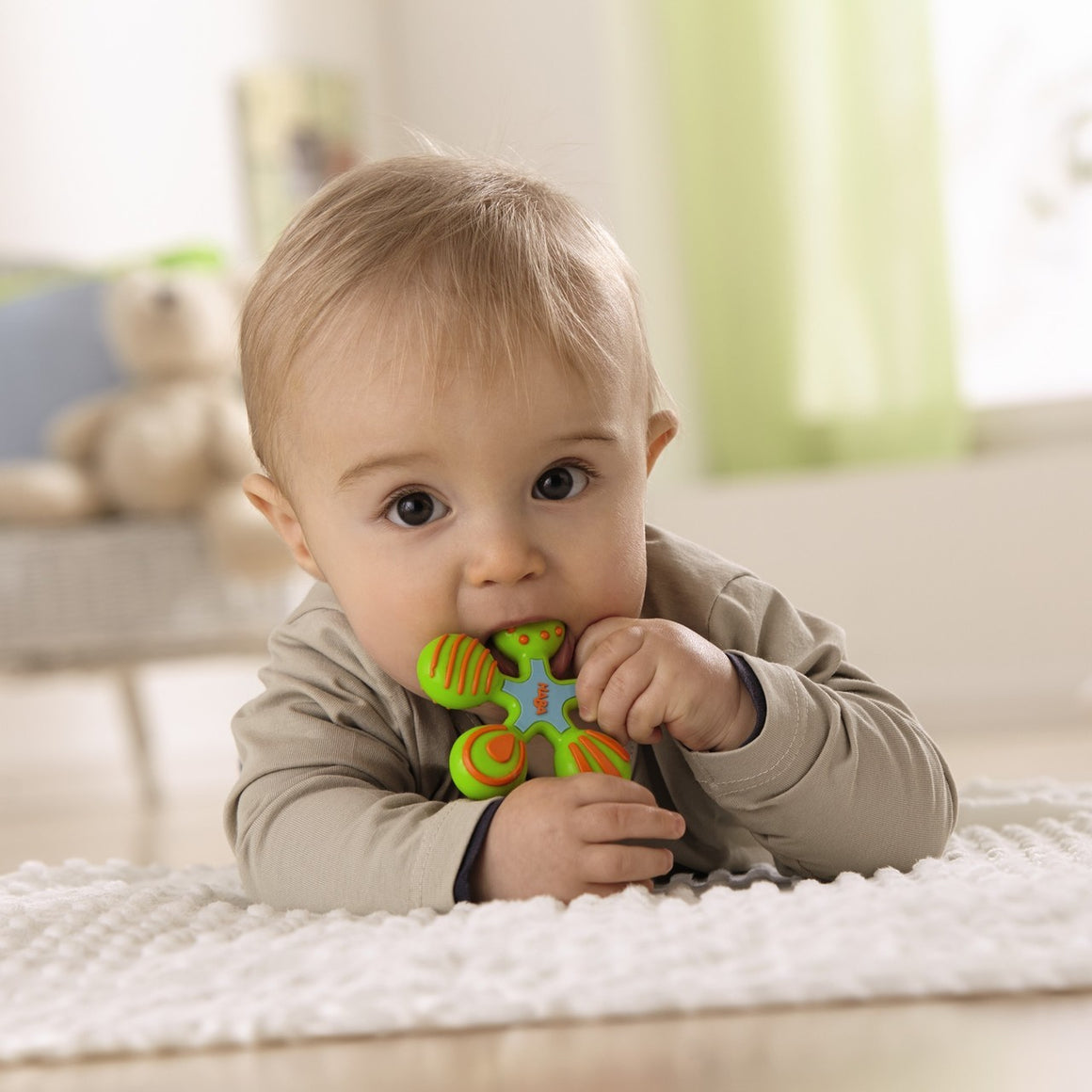 "HABA clutching toy star silicone teether measures 2.75"" diameter in light blue, lime green and orange"