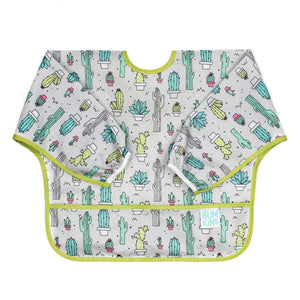 Bumpkins Sleeved Bib in Cacti print features yellow, blue and neutral cacti on a white background with yellow piping on seams