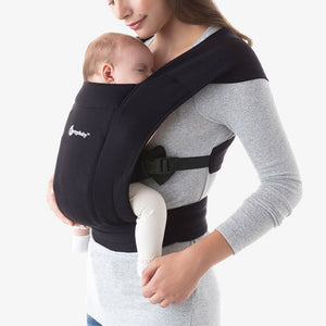 woman carrying an infant in an oxford blue ergobaby embrace baby carrier