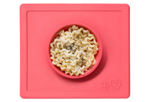Happy Bowl by EZPZ, shown in coral red with pasta inside, made from silicone
