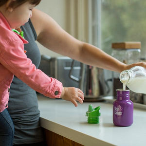 winter plum klean kanteen sippy cup being filled with milk for a toddler