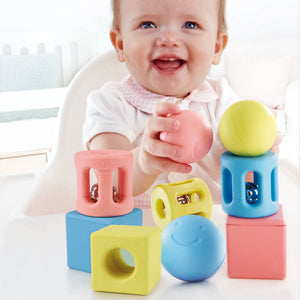 hape geometric trio rattle set contains 9 pieces in blue, yellow, and pink