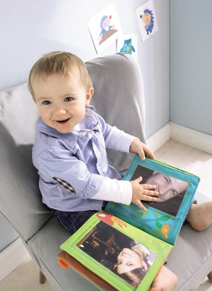toddler enjoying the photos in the First Photo Album Friends of the Enchanted Forest by Haba