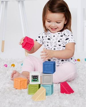 toddler girl playing with the skip hop vibrant village squeeze blocks set that includes 9 brightly colored squeezable blocks in various shapes