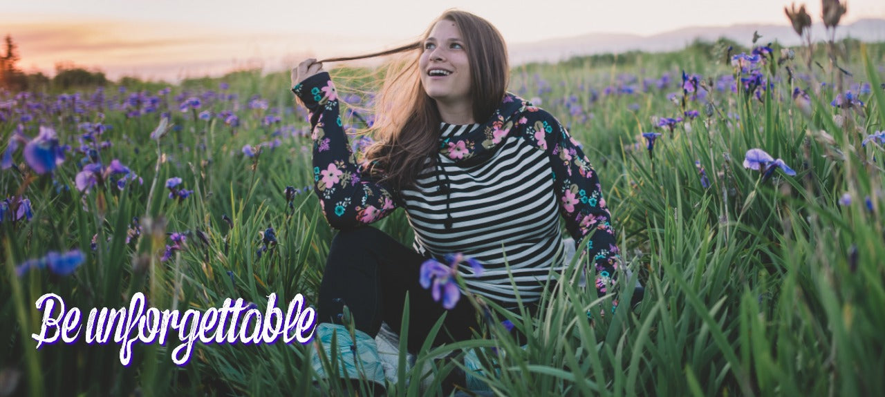 girl sitting in iris field wearing striped floral hoodie