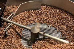Coffee roaster with coffee beans roasting close up