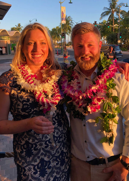 Couple during sunset wearing colorful flower leis