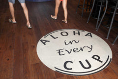 Aloha in Every Cup circle sign on coffeeshop wooden floor