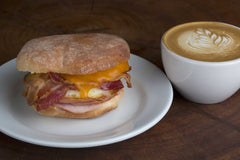 Egg, bacon and cheese English muffin breakfast sandwich close up with latte in a cup
