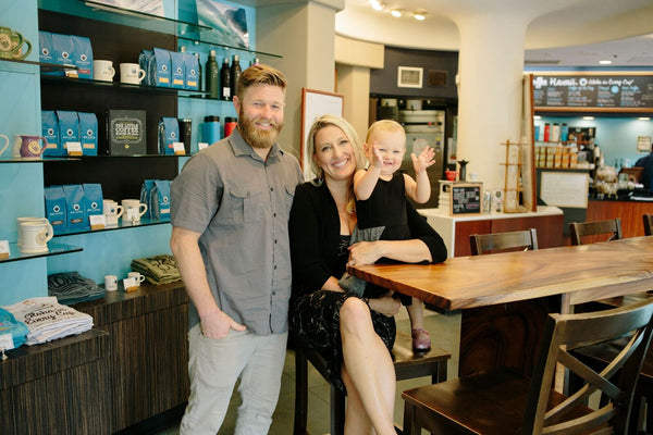 Kai Coffee Hawaii owner family - Sam Suiter, Natalie Suiter and their daughter sitting at a koa wooden table in their surf-inspired upscale coffee shop, Kai Coffee Hawaii