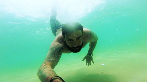 Man with beard swimming underwater