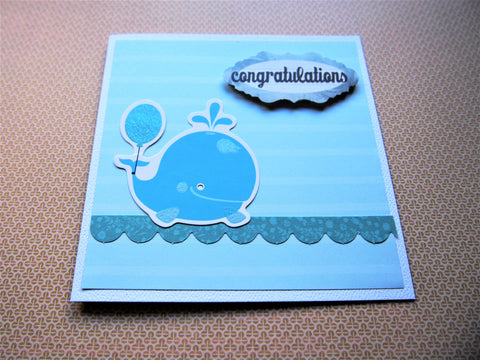 Baby boy congratulations card in light blue with cute whale nautical design