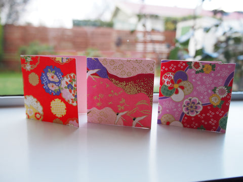 Origami paper gift tags on pink cardstock