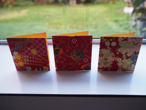 Origami paper gift tags on orange cardstock