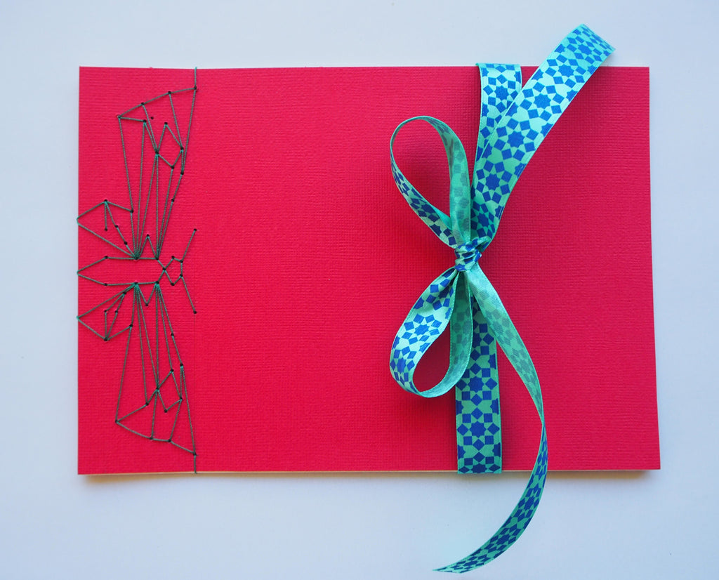 Festive special: notebooks with unique hand-bound decorative designs in red with butterfly binding