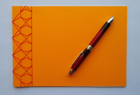 Festive special: notebooks with unique hand-bound decorative designs in rich yellow with kissing fish binding