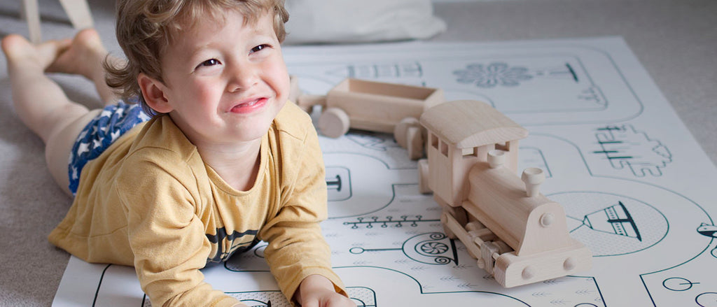 child with wooden train