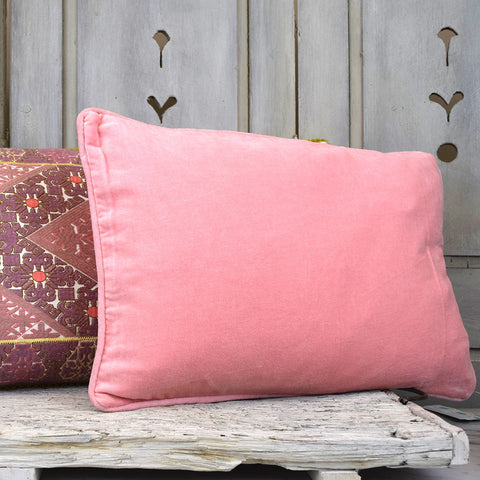 Coral coloured velvet cushion