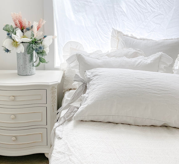white linen pillow with a girl sleeping on it and a gray ruffle top sheet